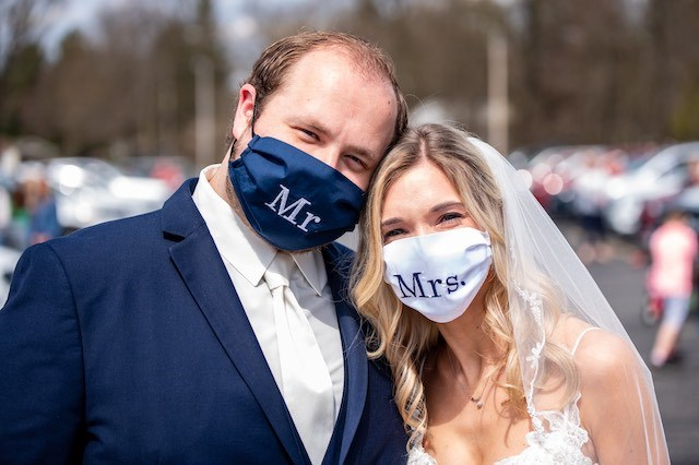 Alexis Benyo and Conor Chrystal of Austintown wore masks made by her grandmother for their social distancing reception on Saturday at St. Joseph Parish on New Road. (Shaun Jordan Photography)