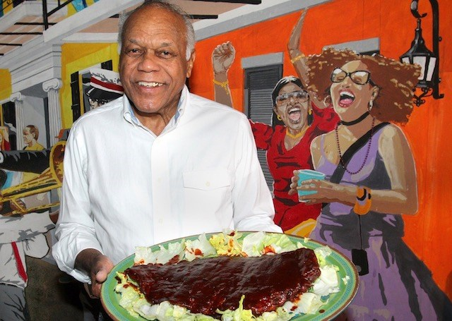 Charlie Staples, owner of Charlie Staples Famous Bar-B-Que, holds a plate of barbecue ribs at his Youngstown eatery. (Photo by William D. Lewis)