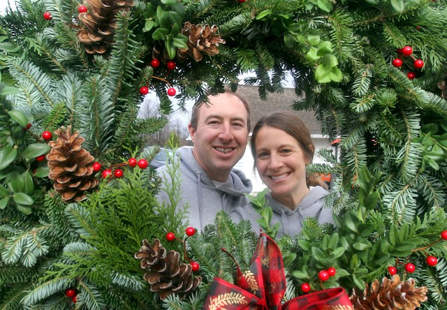 Jon and Tara Fodor, owners of Fodor Tree Farm in Poland, are framed in a wreath at their farm. (William D. Lewis)
