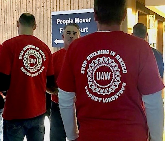 "Clad in red, former GM Lordstown Assembly Plant workers have lined the entrance to today's meeting in Detroit, chanting ""No product, no vote,"" to all who pass. Photo by Jess Hardin"
