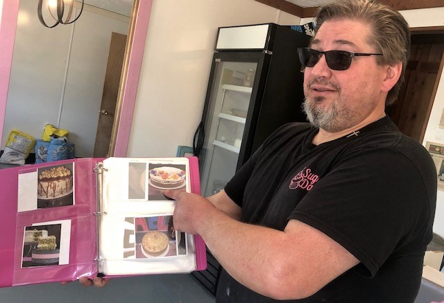 Abigail's Bakery Creations owner Bill Smith flips through a photo album of custom order cakes. Smith said he has made more than 50 cake flavors to appease his customers. (Alyssa Weston/Mahoning Matters)