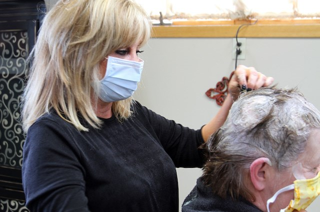 Sheri Altobelli, an employee of Strands Hair Studio in Niles, was at work Friday, May 15, 2020, the first day Ohio salons were allowed to reopen under relaxed state pandemic restrictions. (William D. Lewis/Mahoning Matters)