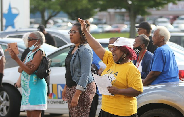 """Community members join in prayer during the """"Stop the Violence"""" community prayer vigil at the former Bottom Dollar Store parking lot Wednesday evening. (Robert K. Yosay 