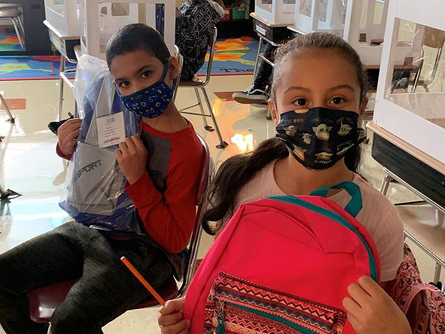 Nandiel Maldonado and Itzel Melendez, fifth-grade students at Taft Elementary School, show their new backpacks that were donated by New Castle, Pa.-based Son of the City. (Contributed photo)