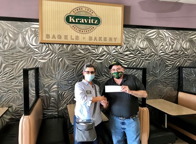 Suzanne Barbati, president and executive director of OH WOW! The Roger & Gloria Jones Children's Center for Science & Technology, accepts a $500 donation from Jack Kravitz, president of Kravitz Delicatessen. (Contributed photo)