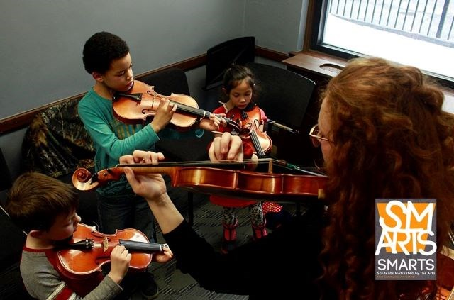 Students play violins in a Students Motivated by the Arts program at Ohio One in downtown Youngstown. (Photo by Lindsay Cameron Photography)