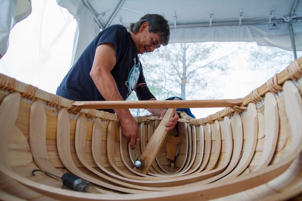 Chuck Commanda works on the canoe.