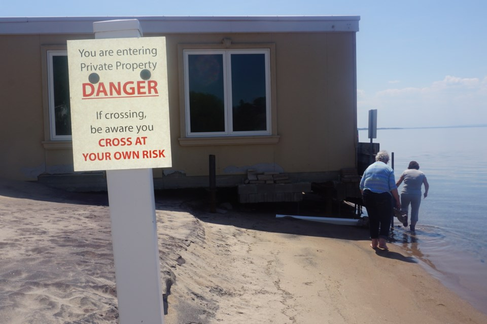 This sign can seen just before the stakes located in front of the boathouse.