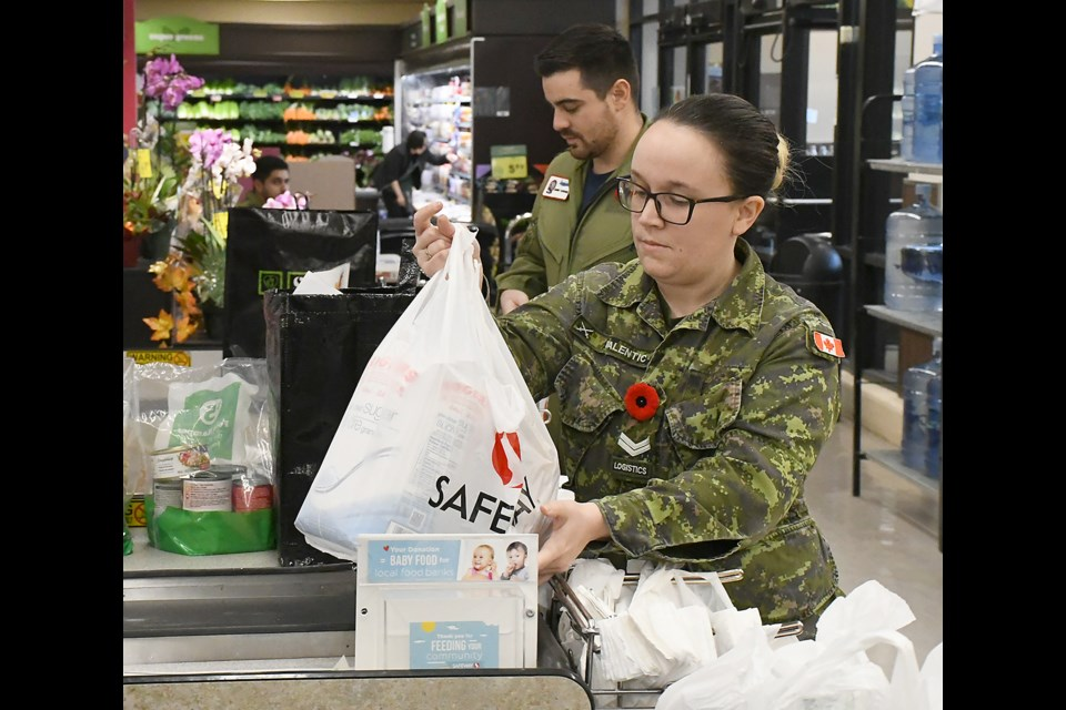 Cpl. Valtenic (front) and 2nd Lieut. Sowchuk bag groceries at Safeway on Friday afternoon as part of their fundraising drive.