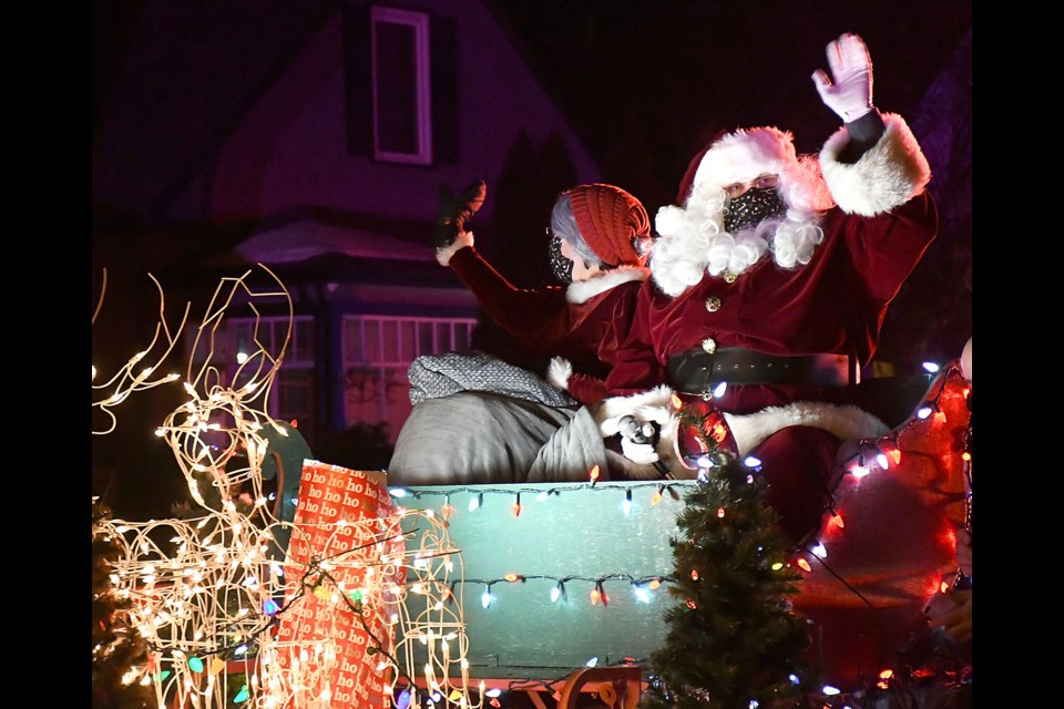 Santa and Mrs. Claus wave to youngsters looking on from their homes and the sidewalk as the Kinsmen Santa Tour makes its way through South Hill on Saturday night.