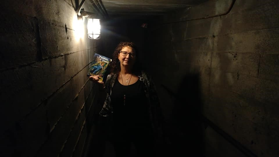 Author Mary Harelkin Bishop poses with a copy of the updated edition of her bestselling novel Tunnels of Time, in the actual Tunnels of Moose Jaw. (supplied)