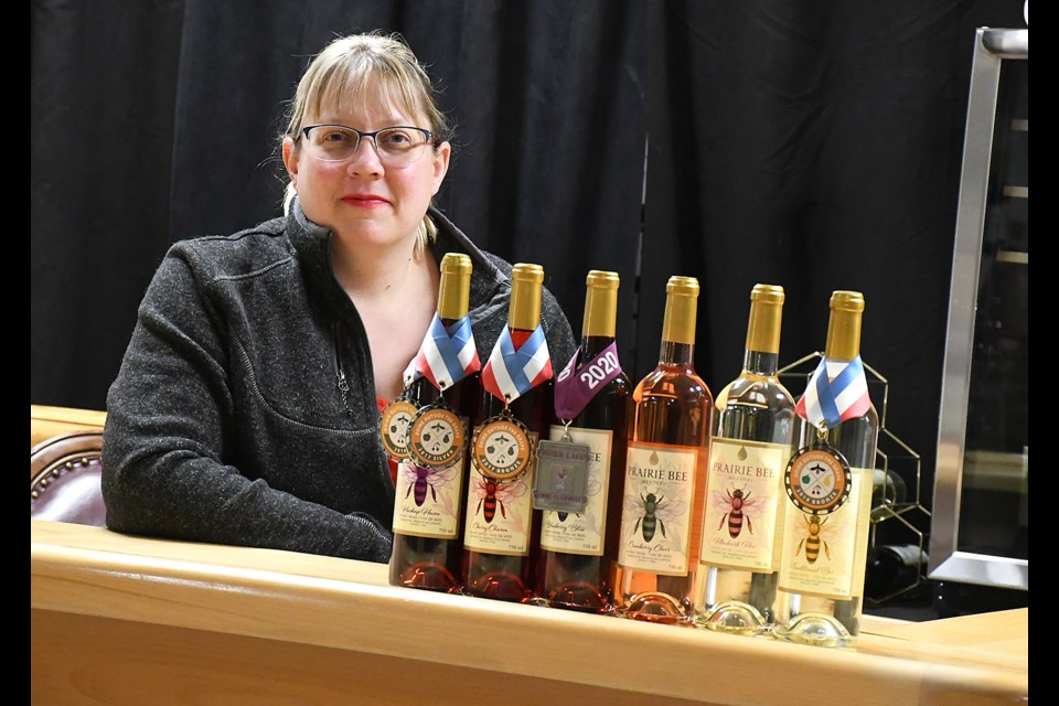 Crystal Milburn with some of Prairie Bee Meadery's award-winning product in their new Grant Hall location.