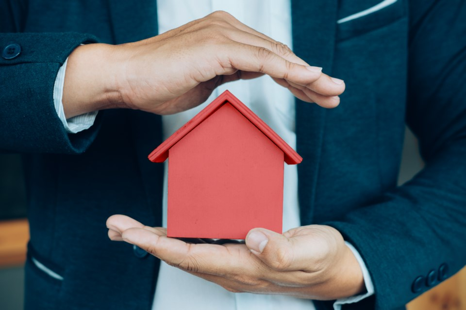 business-man-hand-hold-house-model-saving-small-house