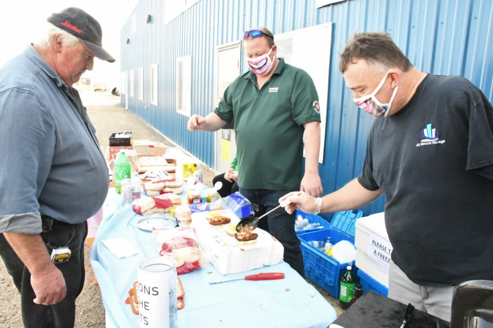 Kent Latimer (right), owner of All Secure Storage, adds onions to Don Firomski's burger, during a barbecue fundraiser on Sept. 21. The event celebrated several company milestones and also helped raise funds for an international Scouting jamboree. Photo by Jason G. Antonio