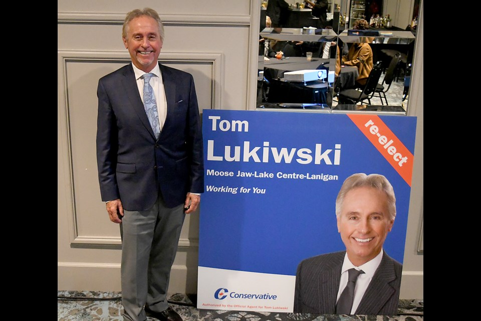 Tom Lukiwski poses with a campaign sign after winning the Moose Jaw – Lake Centre – Lanigan riding.