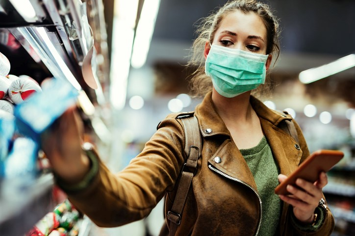 woman wearing mask while grocery shopping getty images