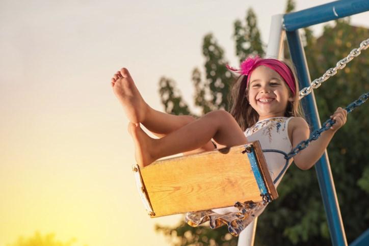 girl swinging playground getty images