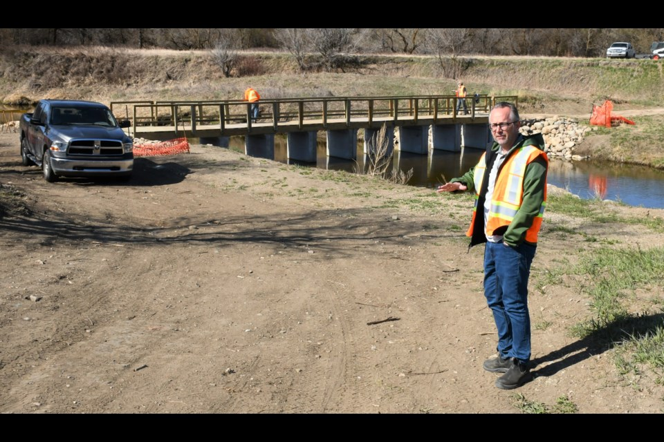 Todd Johnson, general manager of Wakamow Valley Authority, talks about the project to install a new walking bridge near Fourth Avenue South. Photo by Jason G. Antonio