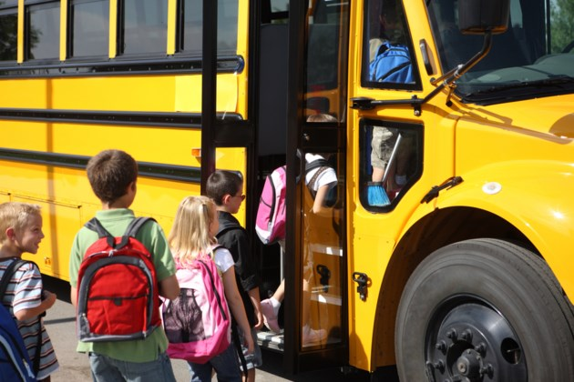 students getting on school bus shutterstock