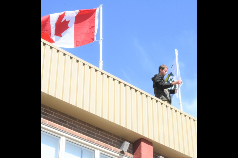 A school custodian at Riverview Collegiate attaches the Treaty 4 flag to the pole. Photo by Jason G. Antonio
