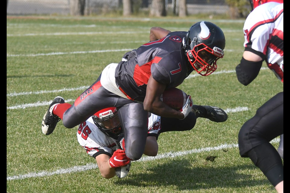 Vanier running back Natan Shiferaw battles for an extra yard or two while being tackled by Weyburn's Alex Junk.