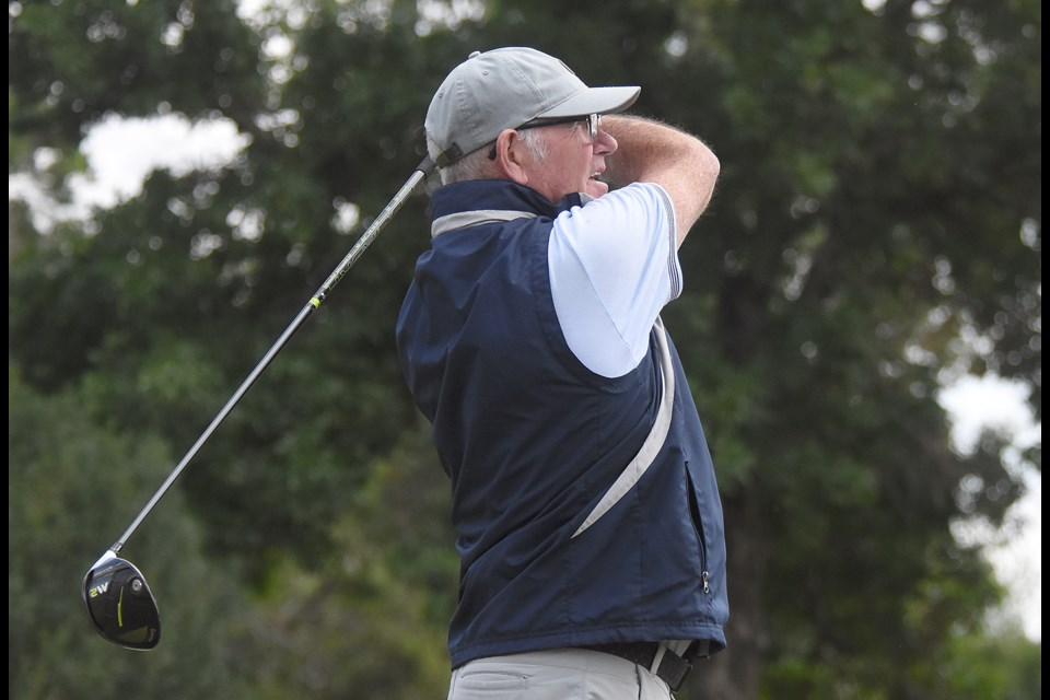 Doug Gillies watches the line on his drive on the 17th hole during the first round of the men's city golf championship Saturday at the Hillcrest Golf Club.