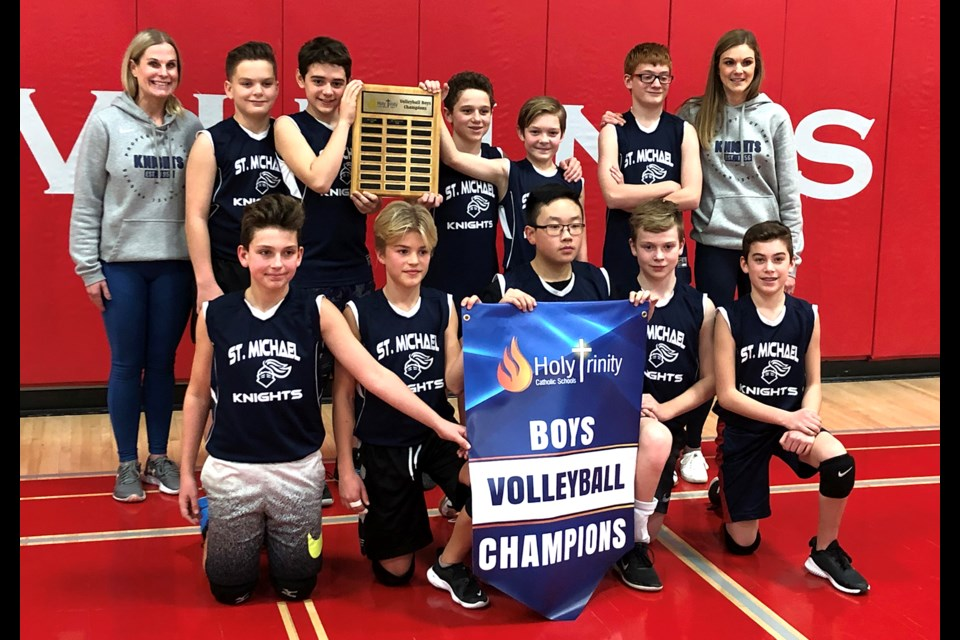 The St. Michael Knights gather for a team photo after winning the Holy Trinity boys volleyball championship.