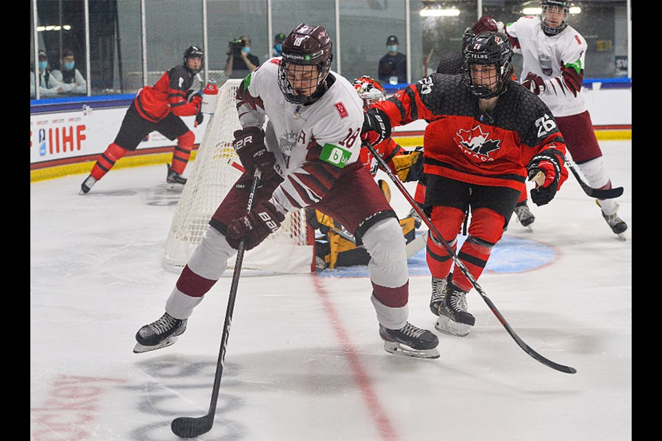 Team Canada and Moose Jaw Warriors defenceman Denton Mateychuk keeps an eye on a Latvia attacker in the corner.