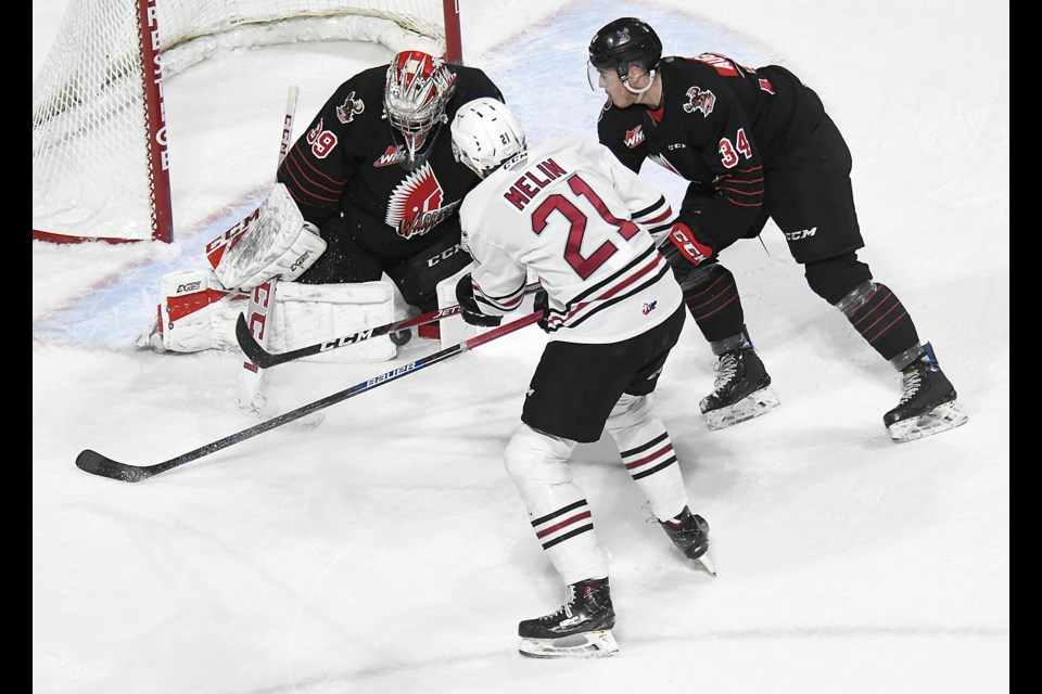 Moose Jaw Warriors goaltender Adam Evanoff stops Dalloon Melin in close as Cayde Augustine covers the play.