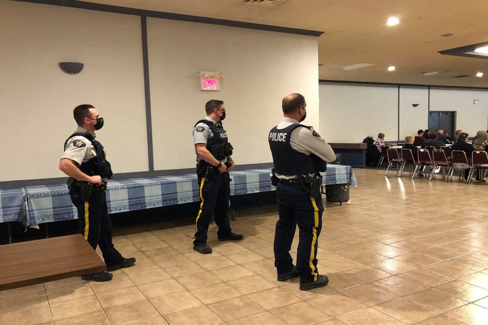 Three Innisfail RCMP officers stand at the back of the Innisfail branch of the Royal Canadian Legion hall moments after arriving following a call from chamber officials.  Dan Singleton/MVP Staff