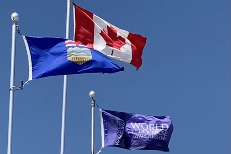 A custom-made flag was on Wednesday, June 16 unfurled and flown alongside Canada and Alberta's banners in front of the municipal office in recognition of World Elder Abuse Awareness Day. The plan to hoist up the flag on Tuesday, June 15 in conjunction with the official recognition of the day had to be postponed due to bad weather.  Submitted photo