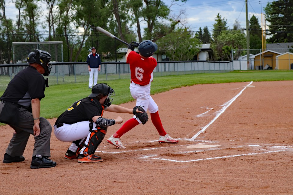 Zach Wilson of the U18 AA Innisfail Hawks takes a mighty swing at the plate during the wild season opening game against the Central Alberta Hounds on June 15 at the Innisfail Aquatic Centre baseball field. The Hounds won 17 to 15. Johnnie Bachusky/MVP Staff