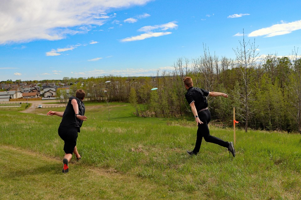 Josh Gette (left) and Chris Snyder jointly release disc throws at an elevated hole at the new Innisfail Napoleon Lake Disc Golf Course. The 23-year-old players designed the course which is expected to be fully ready and open to the public in July. Johnnie Bachusky/MVP Staff