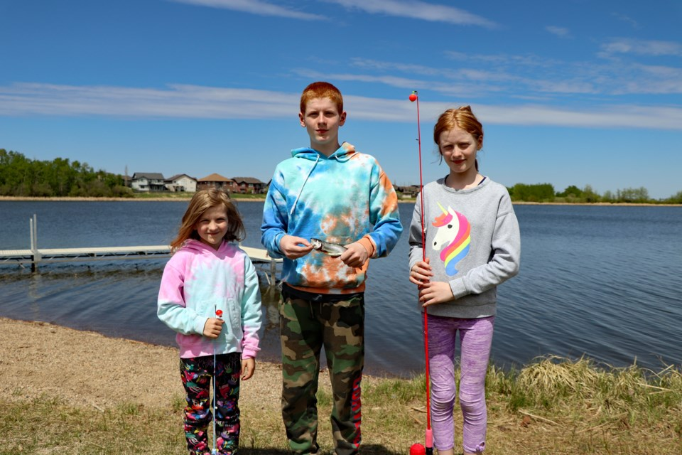 Thirteen-year-old Cian Kelly (centre) holds a caught rainbow trout on May 22 at Dodd's Lake, which was stocked with 330 of the popular sport fish earlier in the day by the Innisfail Lions Club. Cian's angling efforts were joined by six-year-old sister Leah (left) and older sister Michaela, 13. The children and their parents, who came to Canada eight years ago from Ireland, are residents of Cochrane. Johnnie Bachusky/MVP Staff