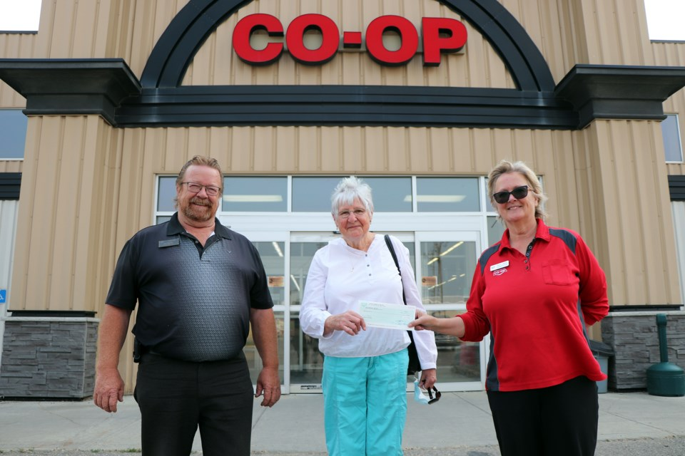 Judy Cooper, co-coordinator of the Innisfail and District Food Bank, centre, receives a cheque for $865 from Co-op's Joe Fletcher, the lumber manager at the Innisfail Farm and Home Centre, and Nancy Crawford, the store's assistant centre manager. Johnnie Bachusky/MVP Staff