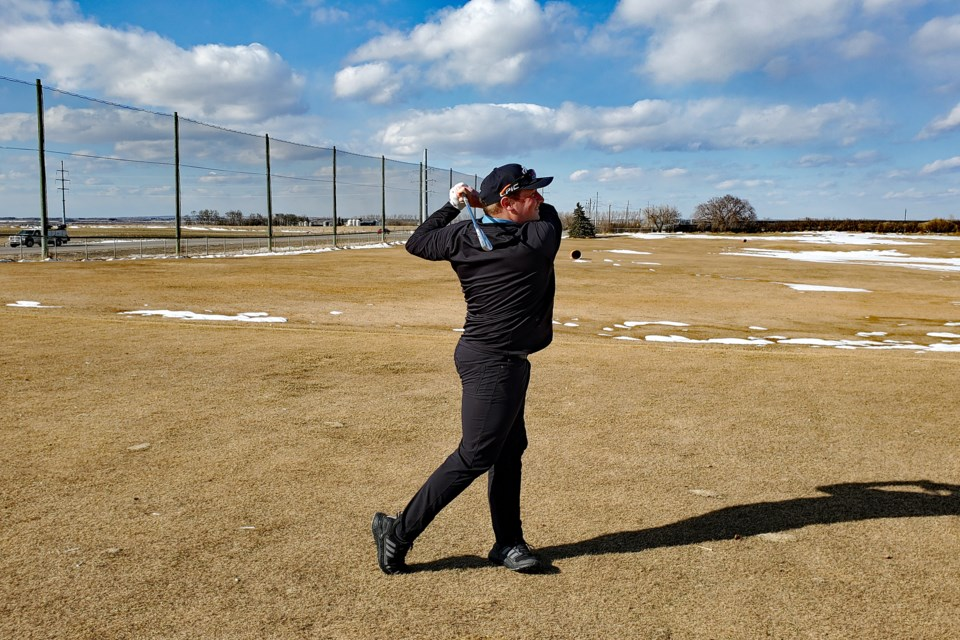Mathew MacDonald, the new head professional at the Innisfail Golf Club, takes a mighty swing last week as the club gets ready for its April 16 opening for the 2021 season.  Photo by Chris Herkel