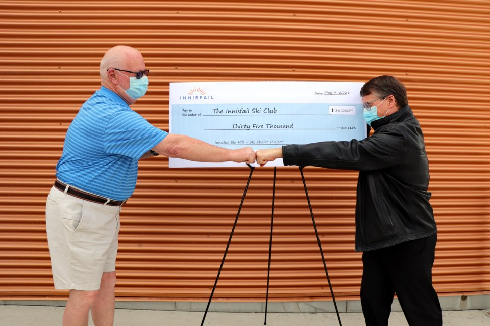 Mayor Jim Romane, left, and Brent Jackson, president of the Innisfail Ski Hill, do a COVID-19 handshake following the presentation of a Town of Innisfail cheque of $35,000 to the ski hill. Last month town council approved the funds to assist the club in the building of the new $385,000 chalet, which is now about 90 per cent complete. Johnnie Bachusky/MVP Staff