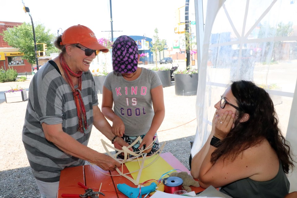 Red Deer County grandmother Joanna Mangan, left, with granddaughter Arianna Aris behind her, helps with lantern creating at an Innisfail Lantern Festival workshop on July 13 at the Market On Main. Johnnie Bachusky/MVP Staff