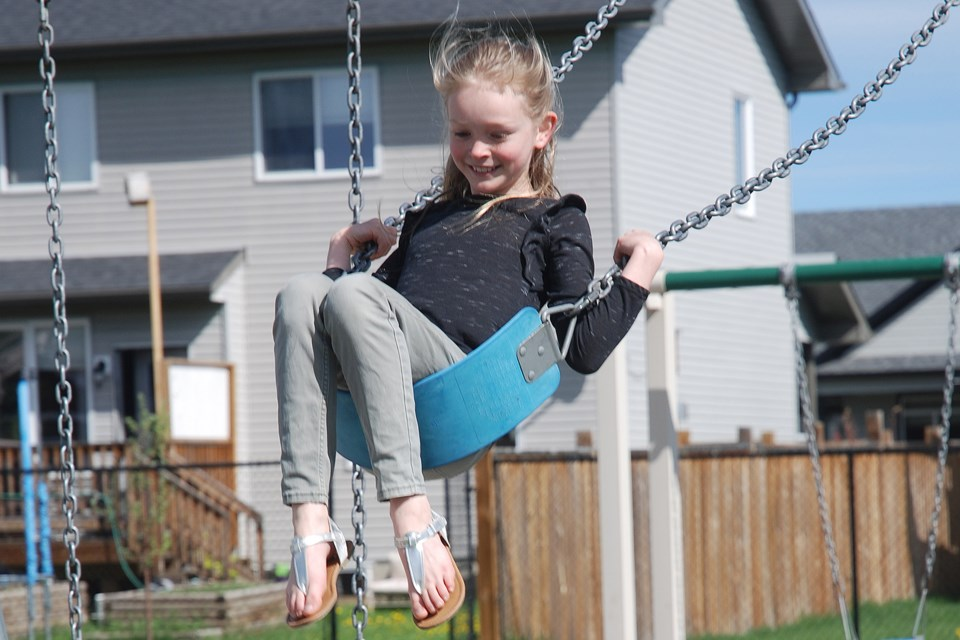 SMILE SAYS IT ALL — Less than one hour after the playground in Sundre's northeast subdivision along 11A Avenue was reopened on Monday morning, Sadie Winters, 9, enthusiastically came out to play on the swings with her sister Georgia, 11, and their cousin Reuben Baber, 12, who was visiting from Balzac.
