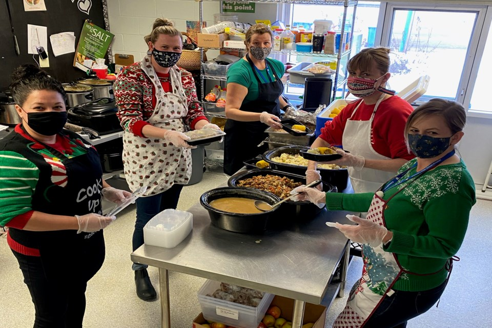 All hands on deck as the staff portion and prepare the turkey dinners for each student and staff member. From left to right is Melissa Rose, administrative assistant; Lisa Baird, school principal; Caroline Tindall, nutrition coordinator; Suzy Argent, educational assistant and Lisa Keeler, educational assistant. Photo by Grade 4 teacher Kristine Horrocks