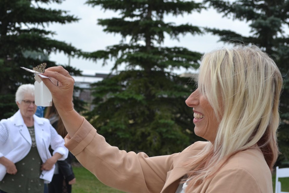 Pastor Melissa Furst  tries to release a butterfly during the Olds & District Hospice Society's butterfly release, held July 17 at the Olds College wetlands. Doug Collie/MVP Staff