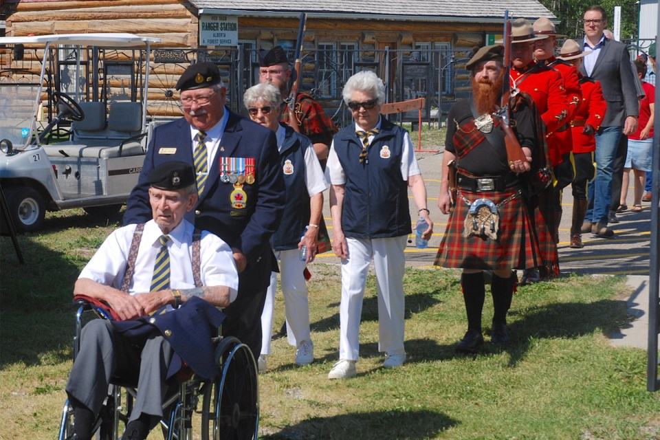 About two dozen people attended the annual Canada Day flag raising ceremony at the Sundre & District Museum's pioneer village. Royal Canadian Legion Sundre Branch #23 member Harvey Shevalier, front, joined the ceremony aided by fellow member Bill Edwards. Members of the Sundre RCMP detachment, local dignitaries, and MLA Jason Nixon, background, also participated.  Simon Ducatel/MVP Staff