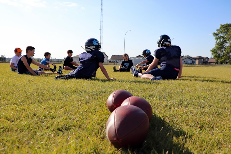Players from the Innisfail Cyclones Bantam team go through stretching exercises during their Aug. 25th practice. Johnnie Bachusky/MVP Staff