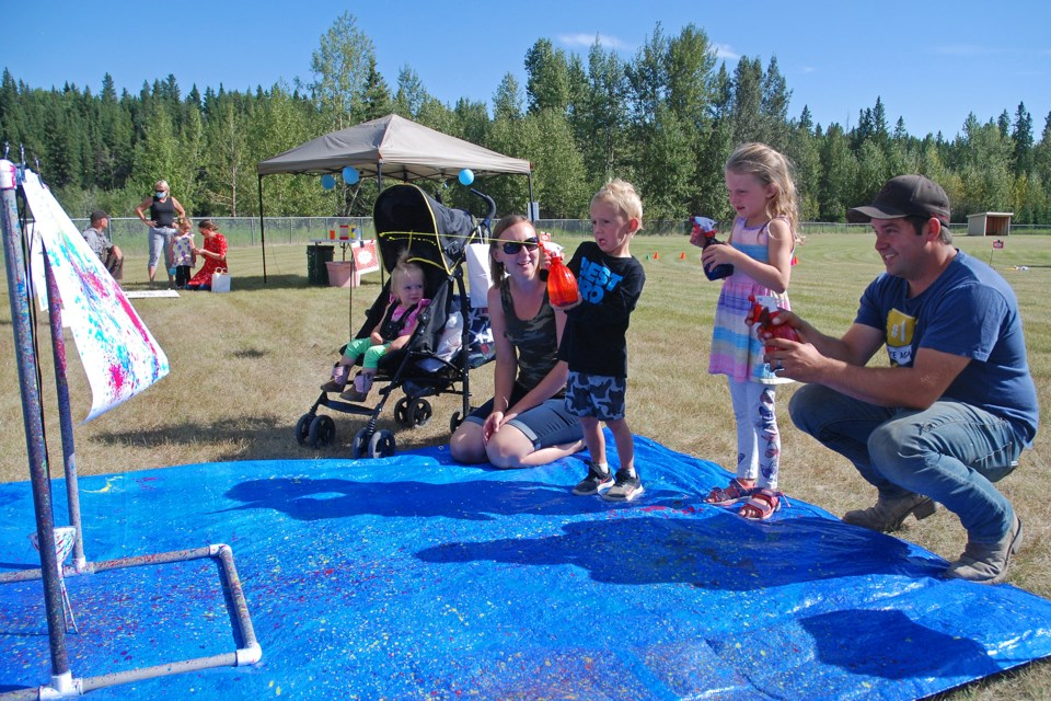 Alexa and Troy Blackhurst, from Sundre, brought out their children Olivia, 1, Chase, 4, and Rebecca 5, to check out the carnival in Sundre. Here, they fire paint-loaded water guns at a canvas to create a colourfully random mosaic. Simon Ducatel/MVP Staff