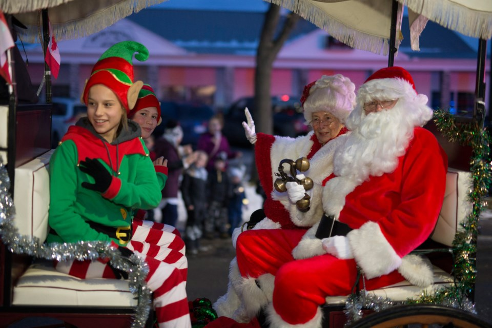 Santa Claus and Mrs. Claus wave as they make their way along the Olds Fashioned Christmas parade route on Nov. 23.  Noel West/MVP Staff