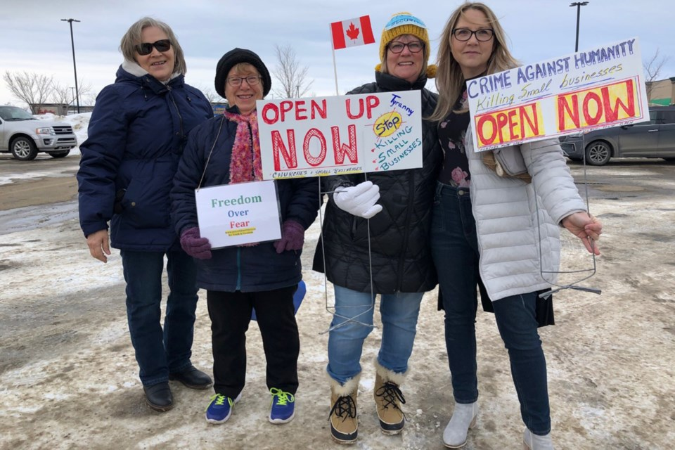 Rally participants hold placards calling for provincial COVID-19 restrictions on businesses to be lifted. It was the second rally sponsored by Mountain View Freedom, the first being in Didsbury on Jan. 30.  Dan Singleton/MVP Staff
