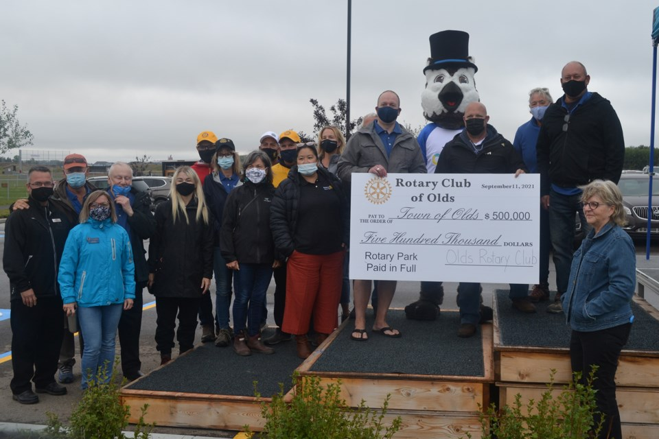 Current Rotary Club of Olds president Paul Gustafson, left, presents the club's cheque for $500,000 to Town of Olds Mayor Mike Muzychka as club members, town councillors and others look on. Doug Collie/MVP Staff