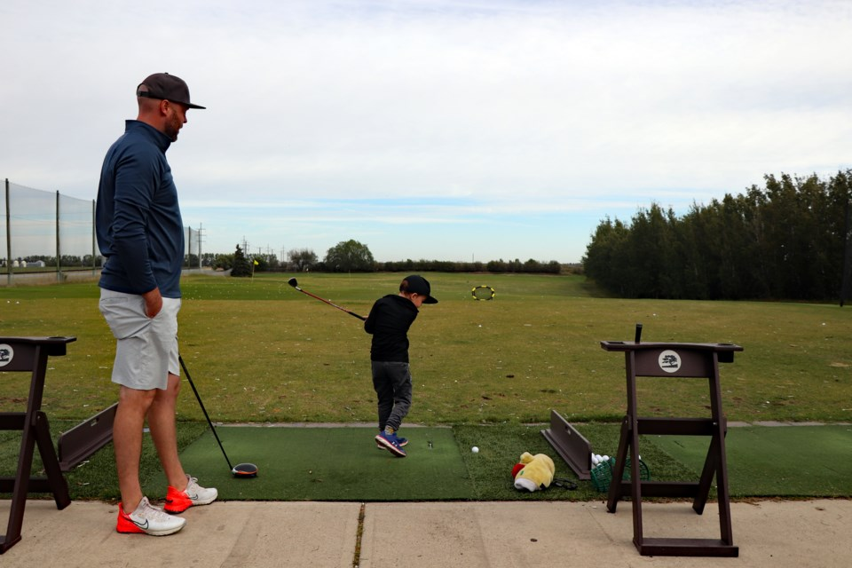 Mike O'Dwyer watches his four-year-old son Graeme take a swing prior to the start of the 35th Innisfail Rotary Charity Golf Classic on Sept. 8. Johnnie Bachusky/MVP Staff