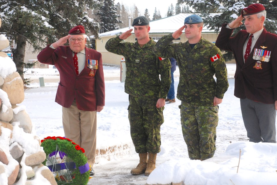 THREE GENERATIONS — From left, Sundre resident Gerry Vida, accompanied by his grandsons Aidan Vida and Taylor Vida, from Red Deer, as well as his son Shandy Vida, right, joined a physically-distanced crowd of more than two dozen people who paid their respects to Canada's veterans and fallen during a minute of silence at the Veterans' Homecoming Park cenotaph in Sundre on Nov. 11. Simon Ducatel/MVP Staff