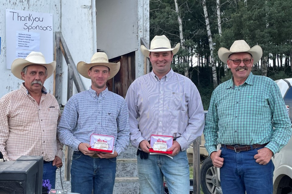 Flanked by brothers Glen, left, and Jim Smith, right, who were representing the Smith family, are first place winners Craig Lynch and Luke Smith.  Submitted photo
